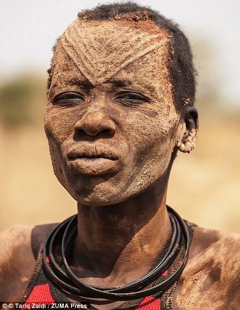Một phụ nữ Mandari bôi đầy tro phân bò khô lên mặt để chống côn trùng và chống nắng.