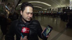 Anh Hassan Shadkhoo cho thấy ảnh vợ trong điện thoại. Ảnh: CBC.