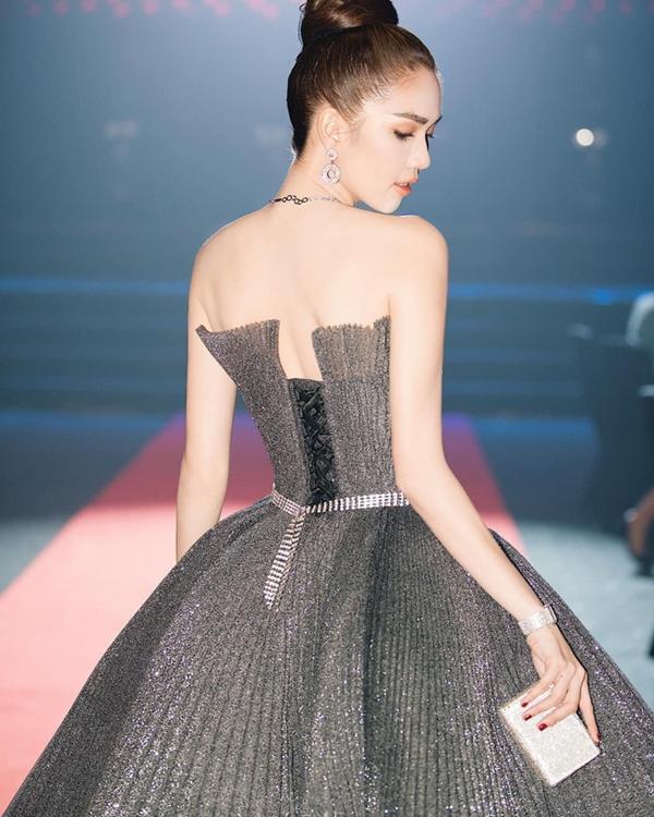 Trước đó, tại lễ trao giảiWebTVAsia Awards 2019,Ngọc Trinh cũng trở thành tâm điểm của sự chú ý khi diện đầm công chúa nền nã của NTK Chung Thanh Phong. Thiết kế phom dáng bồng bềnh, phủ một lớp kim tuyến màu bạc mang lại cho người đẹp vẻ sang trọng tinh tế. Chiếc clutch cầm tay và bộ trang sức đính đá lấp lánh càng khiến người đẹp thêm phần tỏa sáng.