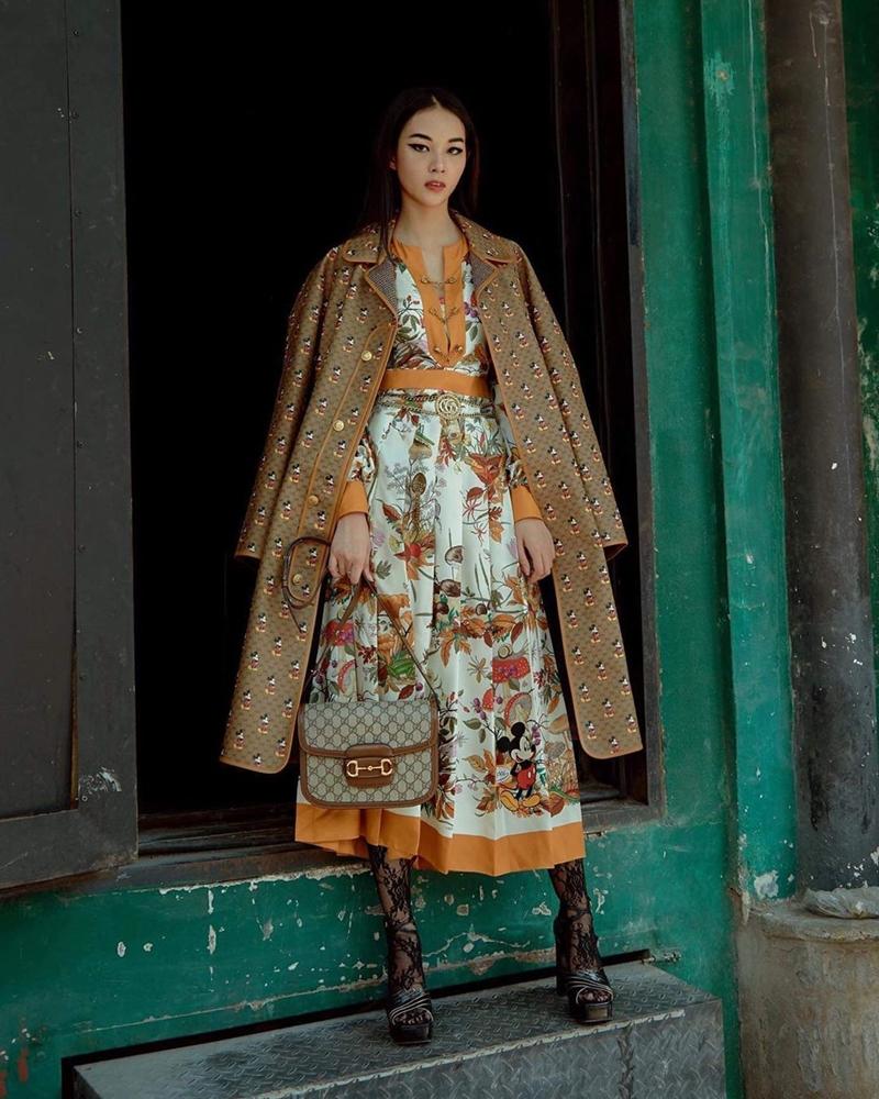 Phí Phương Anh tỏa sáng theo đúng nghĩa đen với bộ cánh hàng hiệu ấn tượng. Người đẹp diện váy họa tiết cùng áo khoác dáng dài họa tiết chuột, kèm phụ kiện túi xách đắt đỏ của Gucci.