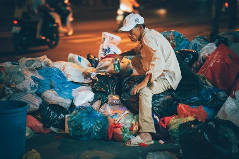 Người đàn ông lọ mọ bên đống rác đêm giao thừa
