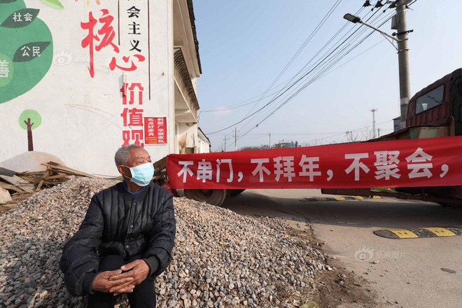 Cụ ông đeo khẩu trang làm nhiệm vụ canh cổng trước cửa thôn Trương Gia Đài. Ảnh: Sina
