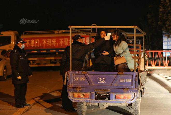 Người dân được kiểm tra thân nhiệt khi ra vào thôn ở thị trấn Tân Quảng. Ảnh: Sina