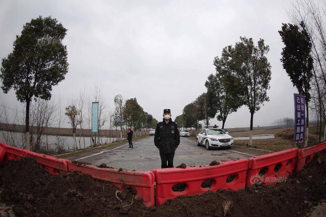 Tuyến quốc lộ tại thị trấn Tân Quảng - hướng đi huyện Giang Lăng bị cấm bằng cách đổ đất. Cảnh sát địa phương đeo khẩu trang trong ca trực. Ảnh: Sina