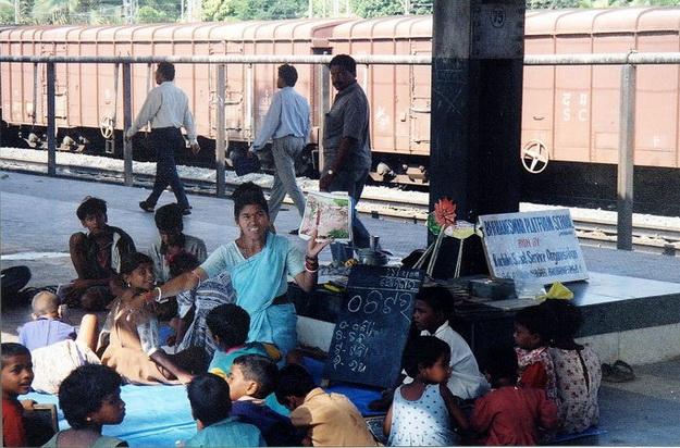 Nhóm học sinh ngồi tụ tập tại ga tàu, nghe giáo viên dạy ở Ấn Độ.