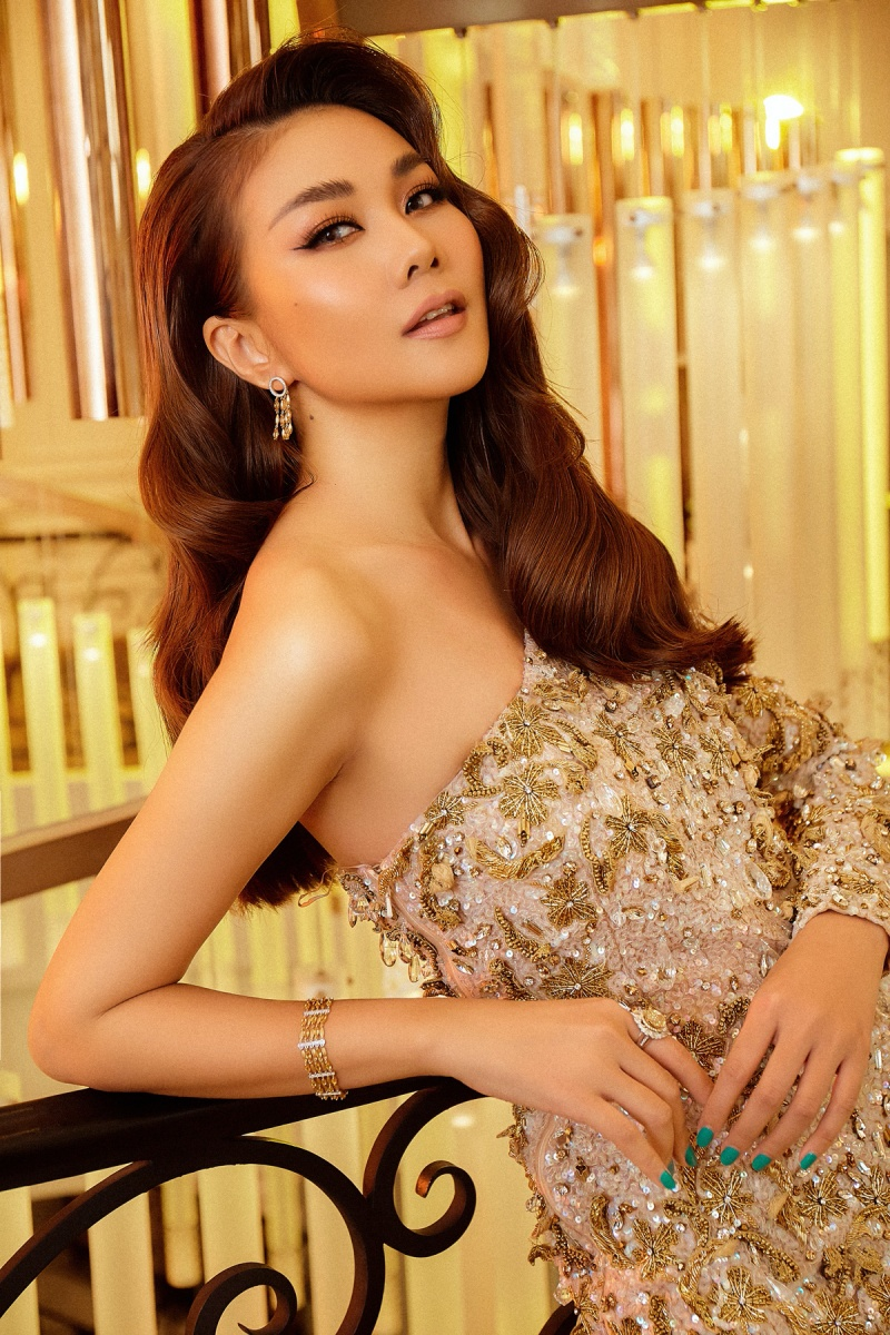 Đầm dài lệch vai mang sắc vàng óng ánh, đính kết tỉ mỉ kết hợp phụ kiện đồng điệu khiến Thanh Hằng trở nên kiêu sa, lộng lẫy hơn bao giờ hết. Kiểu tóc dài lượn sóng,uốn phồng phần mái tăng thêm vẻ sang trọng cho nàng siêu mẫu.