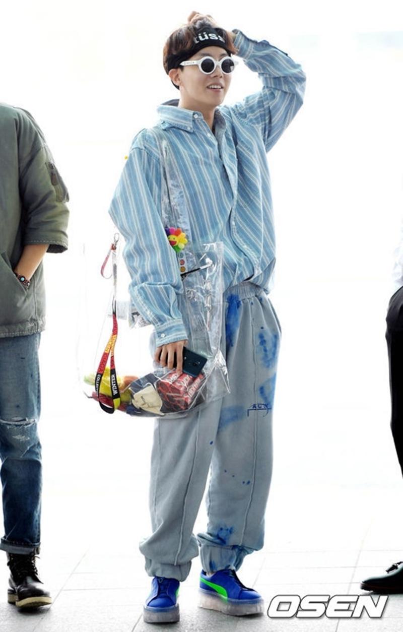 Anh chàng mặc quần baggy thụng cùng áo sơ mi kẻ sọc trắng, mix headband Stussy, kính mát Supreme x Louis Vuitton và giày Puma.