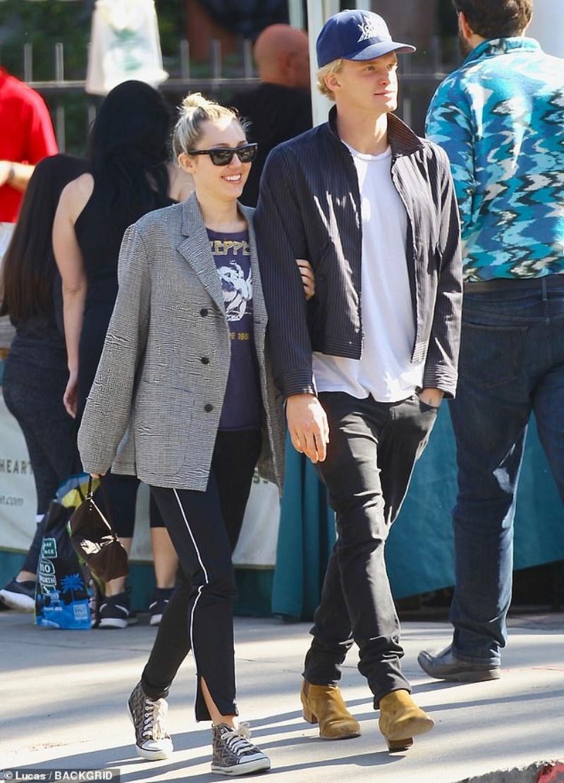 Miley Cyrus và bạn trai Cody Simpson được bắt gặp hôm thứ 7 ở California. Nữ ngôi sao nhạc pop 27 tuổi thể hiện sự say mê không che giấu khi khoác tay ôm người yêu thân mật. Cô mặc một chiếc blazer oversize màu xám và áo phông vintage của Led Zeppelin, quần viền trắng thoải mái và sneaker Converse với họa tiết Fendi.
