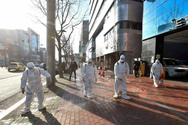 Các nhân viên y tế phun khử trùng nhà thờ Shincheonji tại Daegu, nơi có hàng loạt bệnh nhân nhiễm Covid-19. Ảnh: AFP