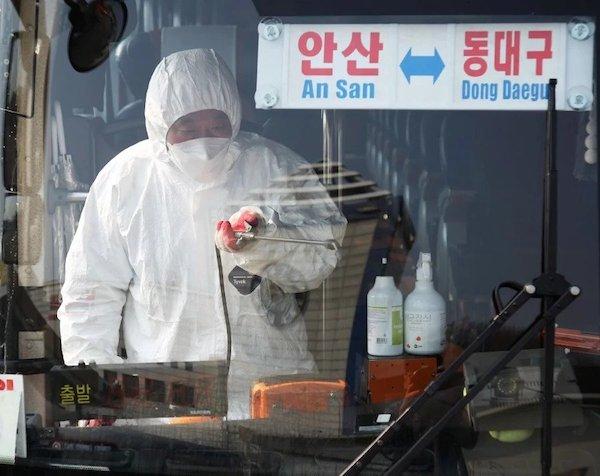 Một nhân viên phun khử trùng xe buýt chạy tới Daegu ở tại ga Ansan, phía nam Seoul. Ảnh: Yonhap