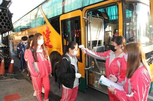 Các em học sinh trước khi lên xe phải đo thân nhiệt