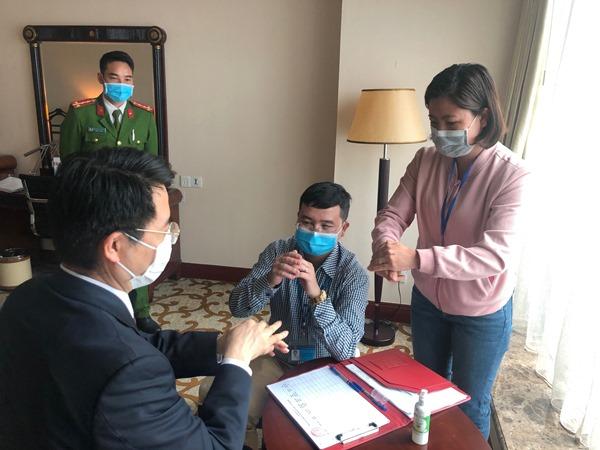 Lựclượng chức năng phường Trung Hòa hướng dẫn người Hàn Quốc cách vệ sinh phòng chống dịch Covid - 19.