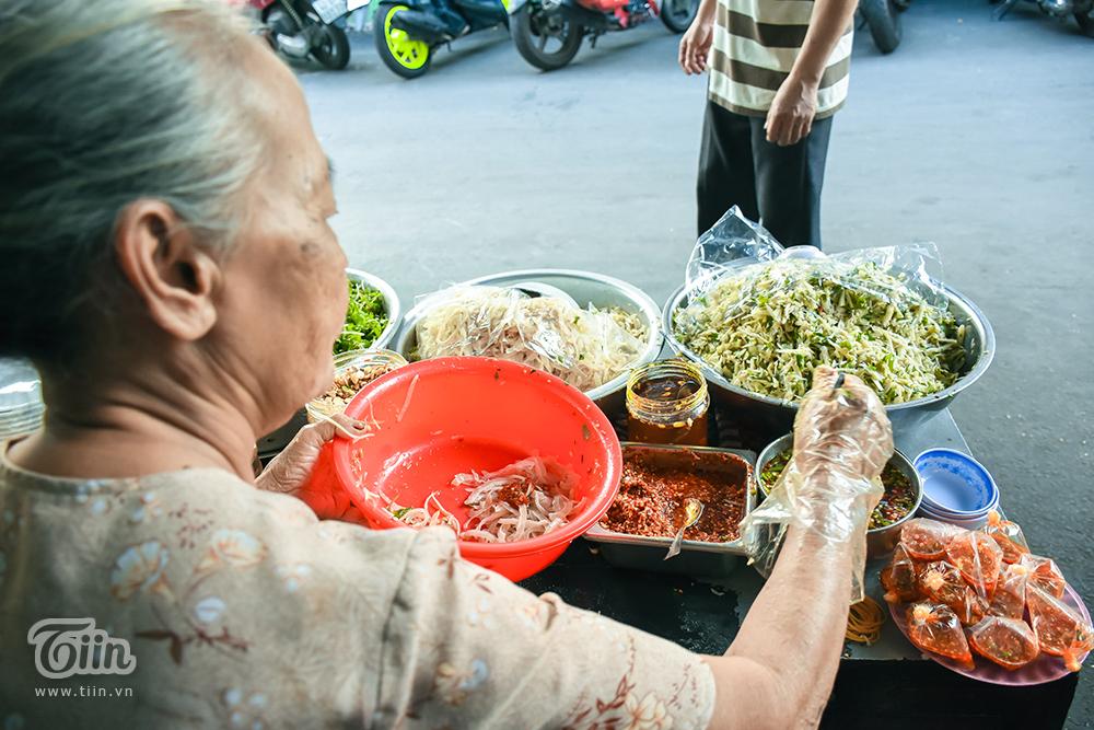 Hơn 30 năm nay, vẫn ở góc nhỏ này, bà Nguyễn Thị Mông (quê Hòa Vang, Đà Nẵng) say mê với quán mít trộn. Không chỉ yêu thích các món do 'bà già' chế biến, các thực khách còn cảm thấy phấn khích khi nhìn hình ảnh một bà lão còn mạnh khỏe, giao lưu hoạt bát với đám trẻ, tay chân thoăn thoắt bán hàng dù ngày nắng hay ngày mưa.