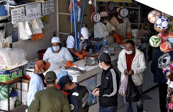 Người dân đeo khẩu trang nhằm phòng chống lại sự lây lan của Covid-19 tại một khu chợ ở La Paz vào ngày 24/3. Ảnh: Getty