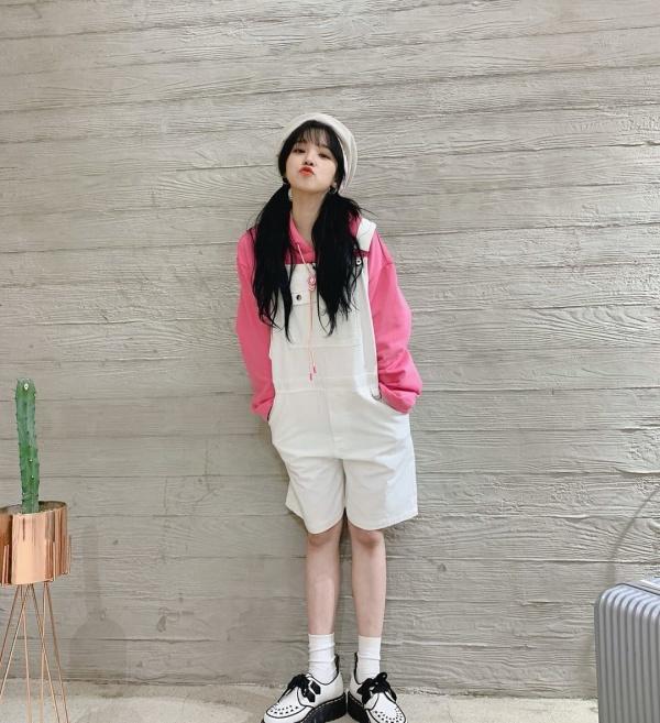 Yuqi (G)I-DLE diện style búp bê đáng yêu với set áo thun hồng, quần short yếm trắng đồng màu với mũ beret, giày platform.