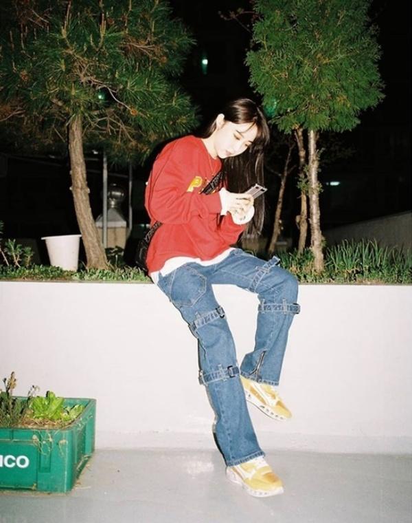 Moonbyul (Mamamoo) chọn style ngầu, sporty với outfit màu sắc như áo nỉ đỏ, quần jeans thắt dây, túi đeo chéo, giày thể thao vàng. Tuy nhiên, cảm giác tổng thể 3 màu sắc được kết hợp không liên quan đến nhau lắm, tạo thành set đồ hơi rời rạc.