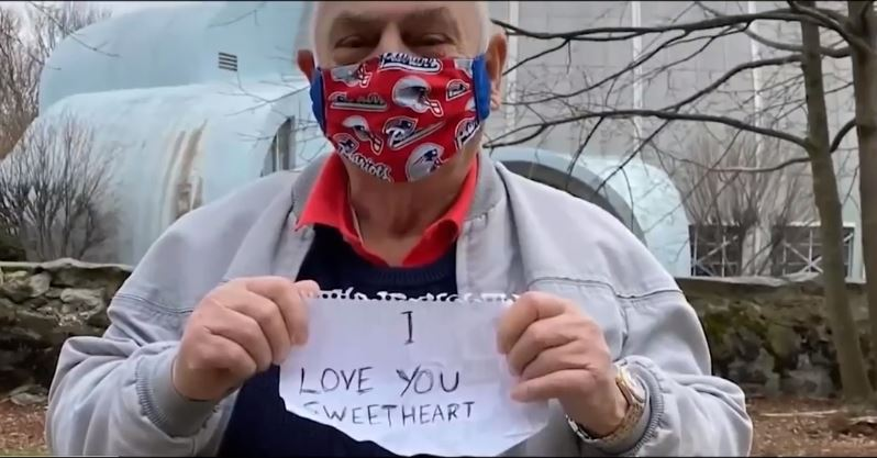 Ông giơ dòng chữ 'Anh yêu em' cho vợ mình qua ô cửa.