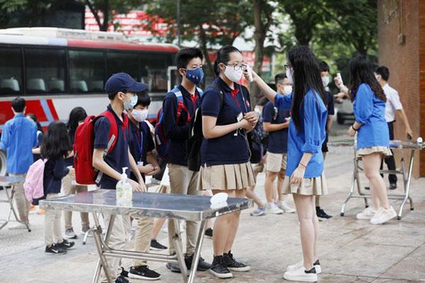 Học sinh được đo thân nhiệt trước khi vào học, hình ảnh đượcThe Straits Times đăng tải.
