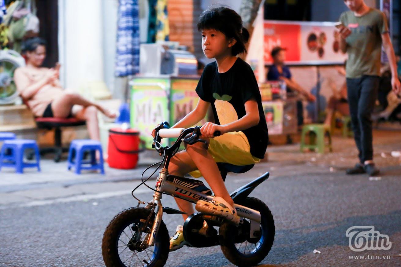 Ở một góc phố vắng khách hơn vẫn có trẻ con đạp xe đạp và chơi đùa