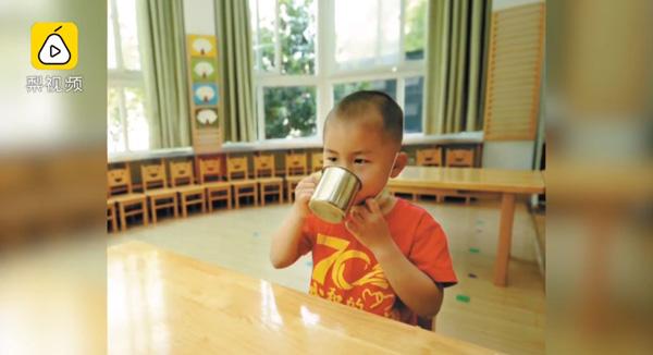 Cậu béđã ngồi ăn cơm và chơi một mình tronglớp học rộng lớn.