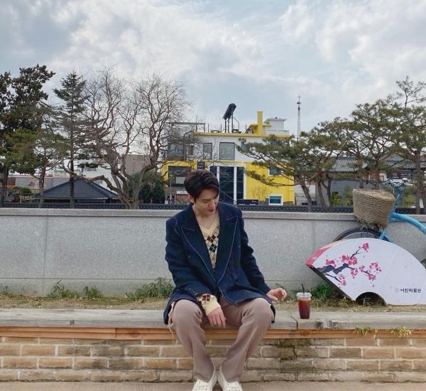 Lee Min Ho ngồi uống nước mà cũng xì-tai hết sức với áo len, quần len nâu và áo khoác jeans mỏng.