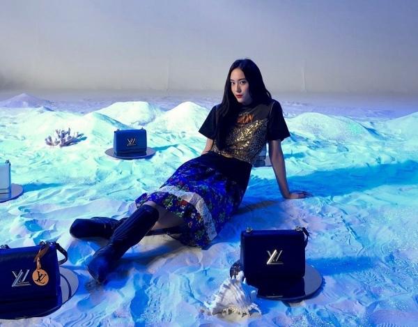 Set đồ của Krystal hơi rối với áo hai dây ánh kim mặc ngoài t-shirt, chân váy nhung họa tiết hoa lá đính ren và boots cao.