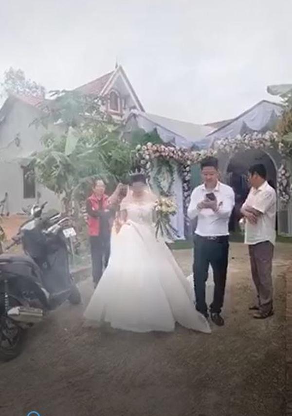 Chú rể vui cười hớn hở trong khi cô dâu đang xách váy cưới nặng nề.Ảnh cắt từ clip.