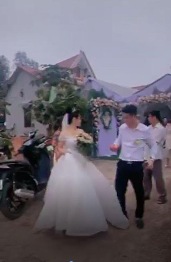Cô dâu cảm thấy khó chịu khi chú rể dẵm vào váy cưới của mình. Ảnh cắt từ clip.