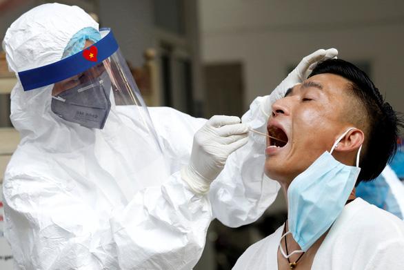 Một chuyên gia y tế lấy mẫu xét nghiệm một hành khách tại một trung tâm xét nghiệm COVID-19 ở Hà Nội hôm 10-8 - Ảnh: REUTERS