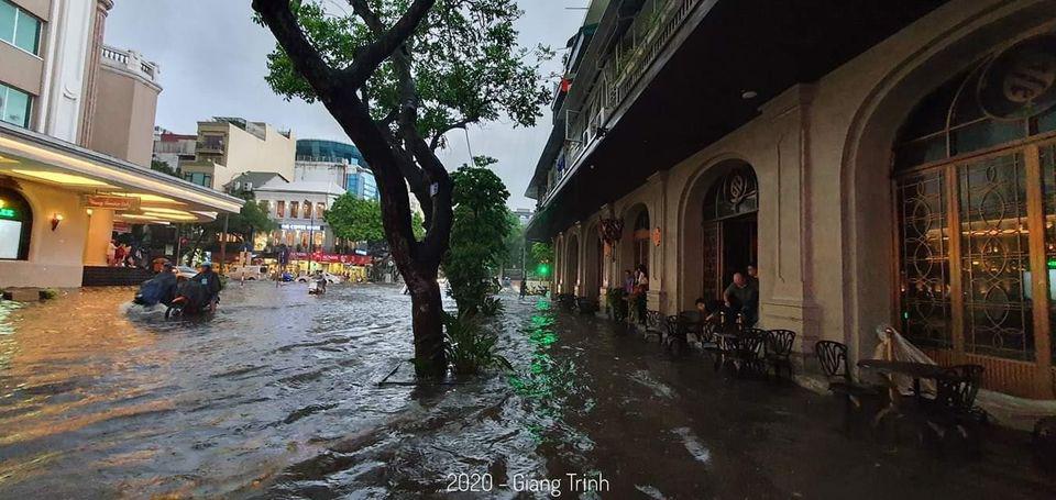 Một số người dân ngồi chờ nước rút và tranh thủ ngắm phố phường ngày mưa lớn.