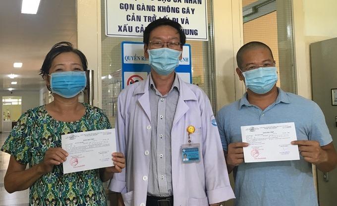 Hai bệnh nhân được trao giấy chứng nhận sức khỏe khi ra viện. Đứng giữa là bác sĩ Nguyễn Thanh Trường - Phó Giám đốc Bệnh viện Bệnh Nhiệt đới TP HCM. Ảnh Thư Anh.