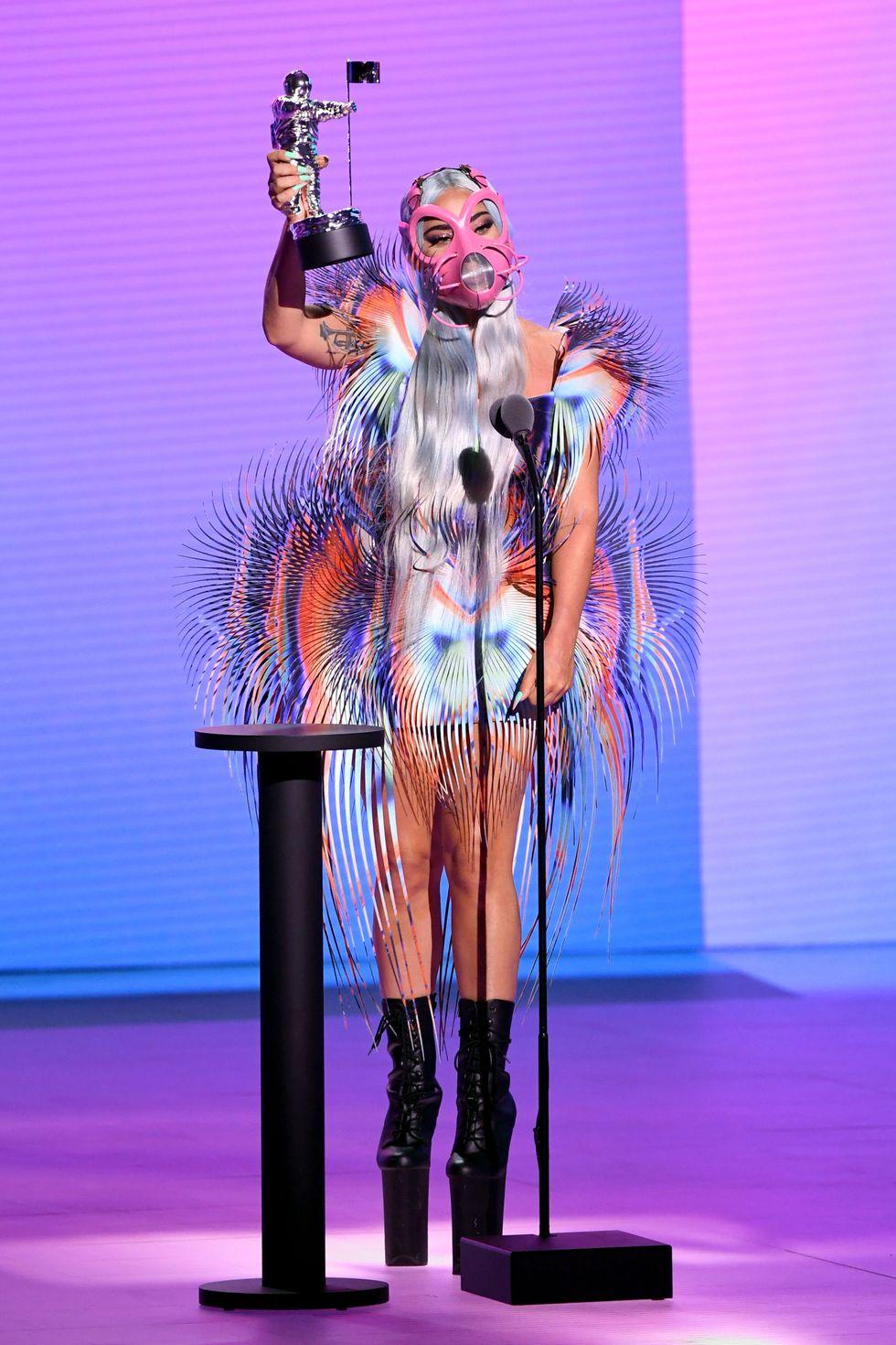 Nhận giải thưởng đầu tiên của đêm giải, Lady Gaga chuyển sang trang phục đa sắc của nhà mốt Iris van Herpen. Nữ ca sĩ đeo thêm chiếc mặt nạ màu hồng, vừa phòng dịch, vừa đảm bảo yếu tố thời trang.
