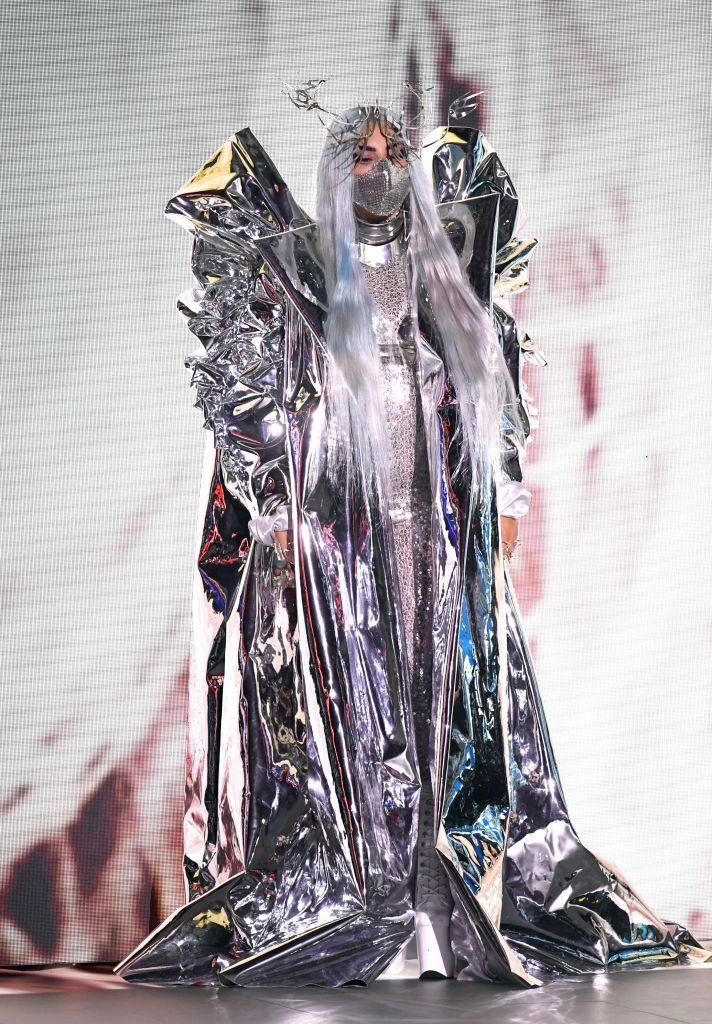 Ở lễ trao giải năm nay, nữ nghệ sĩ quyết định chọn lựa những nhà mốt không quá phổ biến trong làng thời trang. Lady Gaga diện áo khoác của Candice Cuoco, bra và choker đến từ Manuel Albarran, mặt nạ bởi Maisonmet, tạo nên một tổng thể đậm chất tương lai.