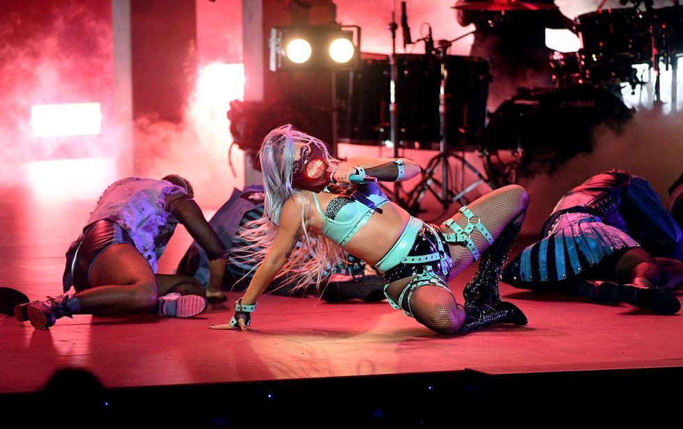 Khi trình diễn 911, Lady Gaga gợi cảm trong trang phục nội y latex màu xanh lá của thương hiệu Vex Clothing. Chiếc khẩu trang kèm màn hình led độc đáo của cô được thiết kế bởi nhà tạo mẫu gốc Việt Michael Ngo.