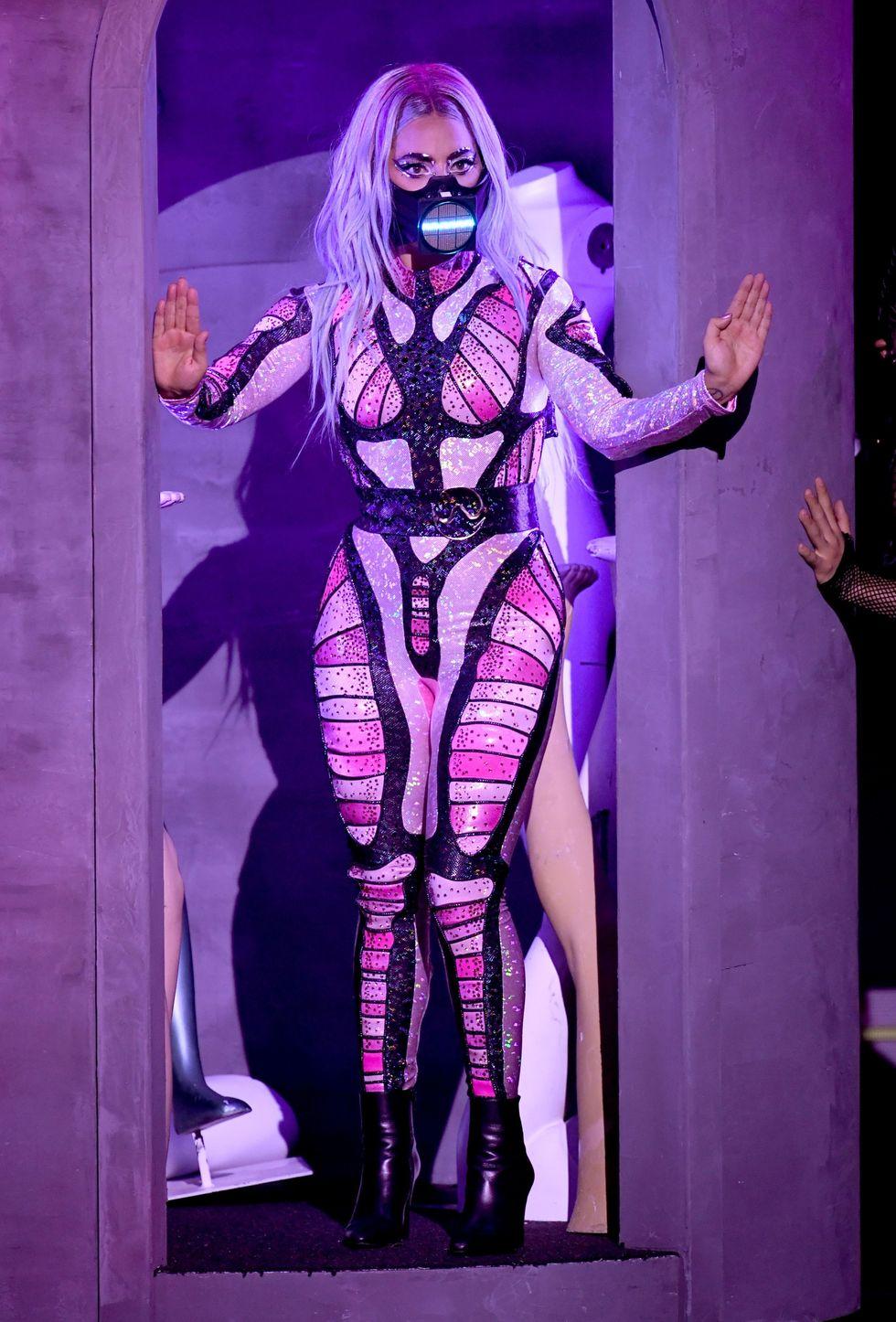 Ở tiết mục Stupid Love, Lady Gaga mặc bộ catsuit đến từ BCalla catsuit, đính kèm thắt lưng Edward Avedis belt, giày Saint Laurent.