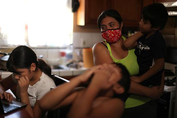 Andrea Ramos (10 tuổi) và em trai Alexander Ramos (8 tuổi), học sinh Khu học chánh Los Angeles đang học trên máy tính do nhà trường phát với kết nối Internet không mấy ổn định. Mẹ các em, chị Anely Solis (32 tuổi) vừa trông Enrique Ramos (5 tuổi) vừa nhìn các con học.