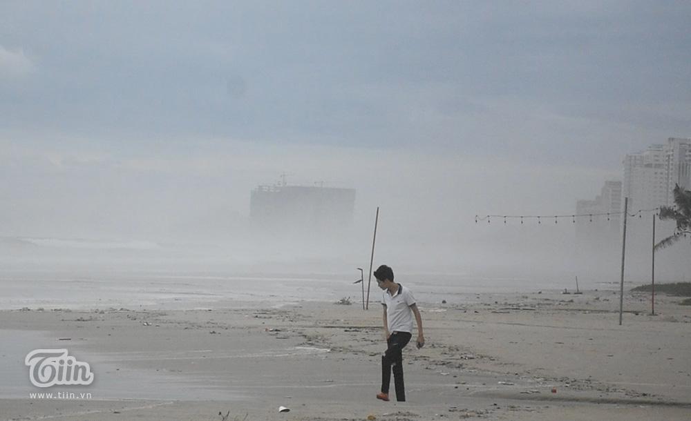 Một thanh niên khác cầm điện thoại đi dạo trên bờ biển.