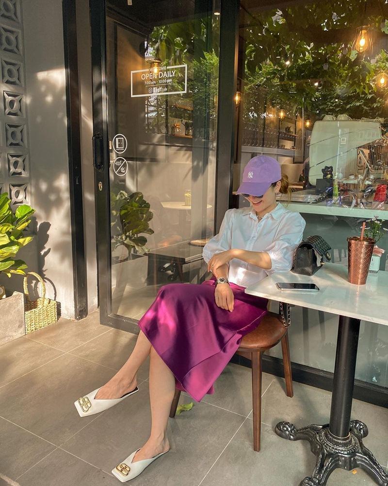 Cặp đôi sơ mi trắngvới chân váy lụa màu hồng tím của Yến Nhi chính là ví dụ. Cô nàng còn điểm trang đôi giày mũi vuôngmũ lưỡi trai và kính mắt đồng điệu để hoàn thiện set đồ.