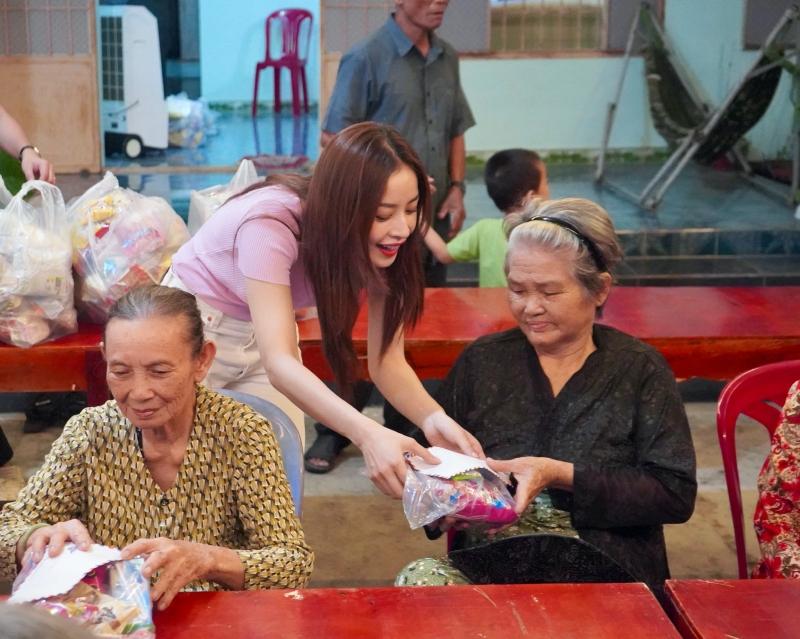 Nữ ca sĩ tự tay trao những món quà đã chuẩn bị trước cho bà con tại chùa.