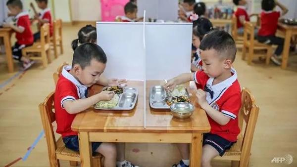 Học sinh mẫu giáo ăn trưa trênbàn có vách ngăn. (Ảnh AFP)