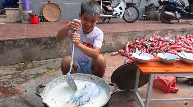 Hưng Vlog trong clip nấu cháo gà nguyên lông. Phía sau là ngổn ngang các vỏ lon nước ngọt.