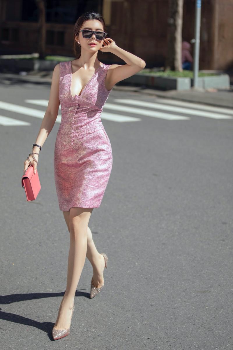 Ở bộ 2, Huỳnh Vy trông nữ tính với bộ váy hồng có những đường may chỉn chu và đối xứng nhau qua hàng nút đính kết tinh tế tạo hình ảnh một quý cô công sở thanh lịch.