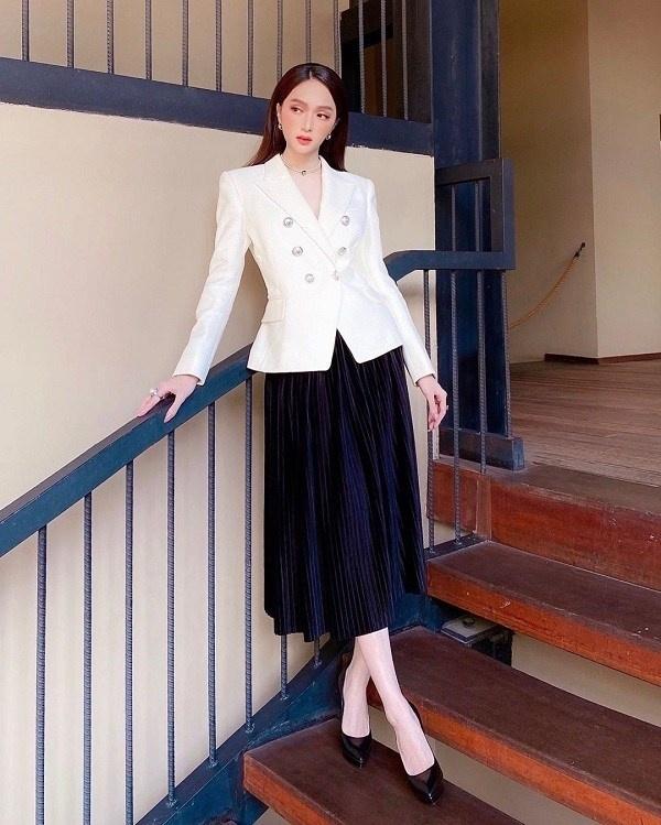 Nếu muốn có vẻ ngoài thanh lịch sang trọng, bạn có thể lựa chọn công thức chân váy midi xếp ly mix cùng blazer như Hương Giang. Nàng Hậu chọn hoàn thiện set đồ đen trắng bằnggiày cao gót tôn dáng, khiến vẻ ngoài càng thêm quý phái, thanh lịch.