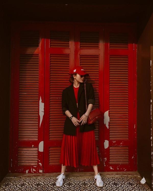 Cũng với công thức na ná Yến Trang nhưng thay vì tông tím, cô em Yến Trang lại lựa chọn cho mình tông chủ đạo trang phục là sắc đỏ rực rỡ. Bên cạnh đó, việc kết hợp chân váy xếp ly đỏ rực với crop top đồng màu, khoác ngoài blazer đen cũng tạo nên vẻ hài hòa, thời thượng cho tổng thể set đồ.