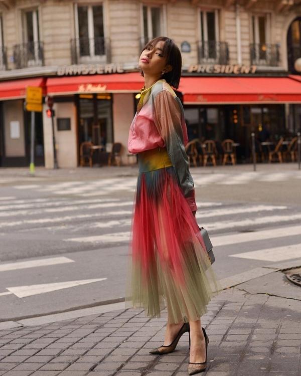 Cũng trưng dụng chân váy midi chất liệu voan nhưng nếu muốn một chút phá cách độc đáo, bạn có thể lựa chọn thiết kế loang màu như của Châu Bùi. Mix item này cùng sơ mi đồng điệu, nàng fashionista khéo léo tạo điểm nhấn cho set đồ thời trang bằng chiếc túi hàng hiệu.