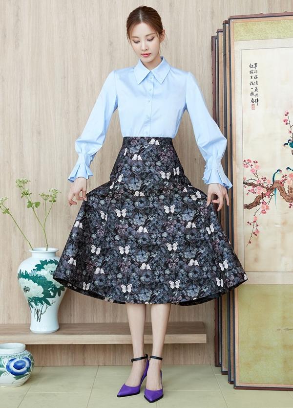 Seohyn đầy thanh lịch, duyên dáng và phảng phất chút cổ điển với áo sơ mi tay loe mix cùng chân váy midi họa tiết, kèm theo một đôi giày cao gót mũi nhọn quai dây.