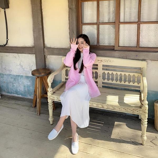 Nếu muốn có phong cáchtrẻ trung và năng động, bạn có thể học theo cô nàng Park Min Young. Mix chân váy midi và áo cổ lọ ton sur ton trắng, nữ diễn viên khoác ngoài áo cardigan màu nổi. Với set đồ này, một đôi giày sneaker trắng hoặc loafer chính là lựa chọn hoàn hảo.
