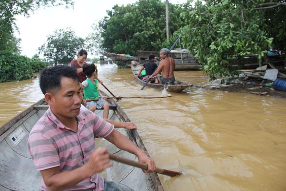 Vợ chồng anh Nguyễn Văn Ái chèo ghe giúp di tản người bị nạn (Ảnh: Trường Trung)