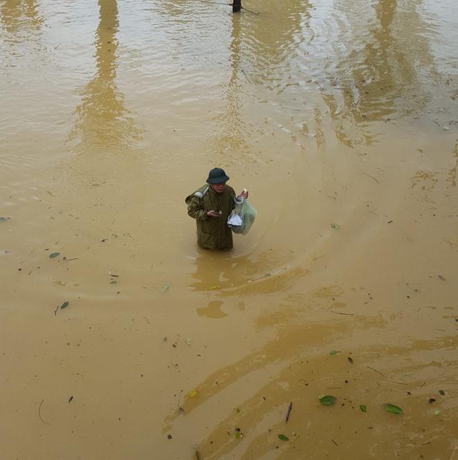 Thầy hiệu trưởng lội qua dòng nước, mang thực phẩm đến tận tay cho sinh viên