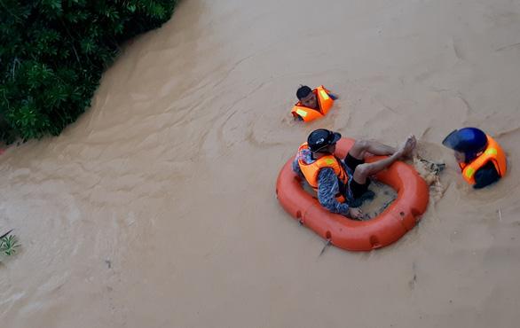 Nhóm thanh niên dũng cảm bơi xuyên dòng nước lũ, cứu trợ những người đang bị kẹt - Ảnh: Phương Thuý